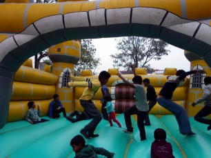 Little girl with the big boys on the bouncy castle in Dehra Dun, India