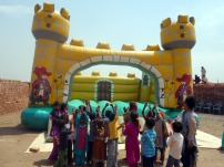 Children cheering for the bouncy castle in the brick kiln near Lahore, Pakistan