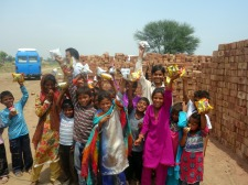 Children cheering for their chips bags in the brick kiln near Lahore, Pakistan
